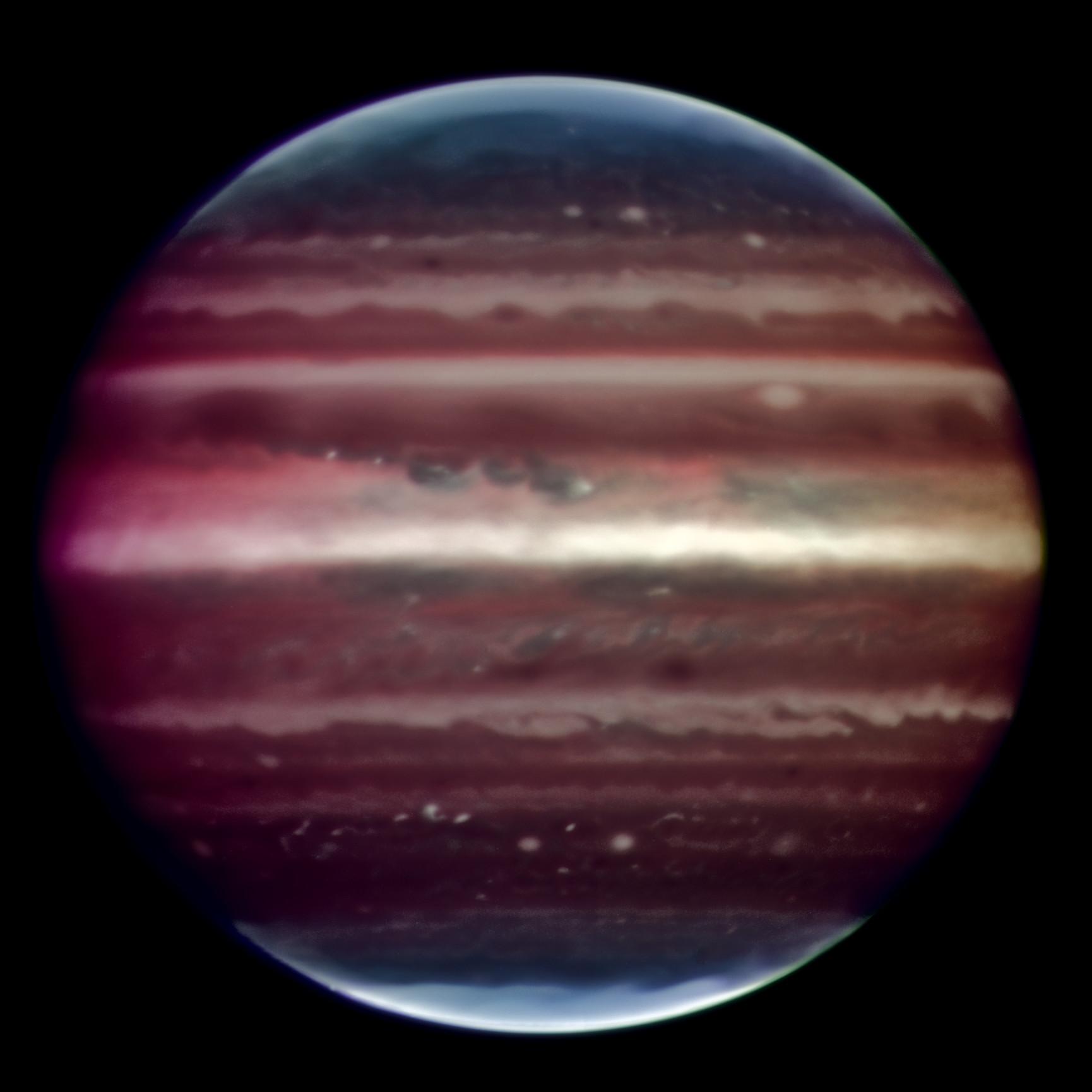 Asombrosa imagen de Júpiter tomada en luz infrarroja en la noche del 17 de Agosto de 2008 con el instrumento prototipo Demostrador de Óptica Adaptativa Multi-Conjugada (MAD) montado en el Very Large Telescope de ESO. Esta foto en falso color es la combinación de una serie de imágenes tomadas durante un lapso de tiempo de aproximadamente 20 minutos, a través de tres filtros diferentes (2; 2,14, y 2,16 micrones). La nitidez de la imagen obtenida es cerca de 90 mili-arcosegundos a través del disco planetario entero, un verdadero récord en imágenes similares tomadas desde la Tierra. Esto corresponde a ver detalles de cerca de 300 kilómetros de ancho en la supericie del planeta gigante. La gran mancha roja no es visible en esta imagen ya que estaba en el otro lado del planeta durante las observaciones. Las observaciones fueron hechas en longitudes de onda infrarrojas donde la absorción debida al hidrógeno y metano es fuerte. Esto explica por qué los colores son diferentes de cómo vemos normalmente a Júpiter en luz visible. Esta absorción significa que la luz sólo puede ser reflejada de vuelta desde las neblinas de gran altitud, y no desde nubes más profundas. Estas neblinas se encuentran en la parte superior muy estable de la troposfera de Júpiter, donde las presiones están entre 0,15 y 0,3 bares. La mezcla es débil dentro de esta región estable, así que las partículas de neblina minúsculas pueden sobrevivir desde días hasta años, dependiendo de su tamaño y velocidad de caída. Adicionalmente, cerca de los polos del planeta, se genera una neblina estratosférica superior (regiones azul claro) por interacciones con las partículas atrapadas en el intenso campo magnético de Júpiter. Crédito: ESO/F. Marchis, M. Wong, E. Marchetti, P. Amico, S. Tordo