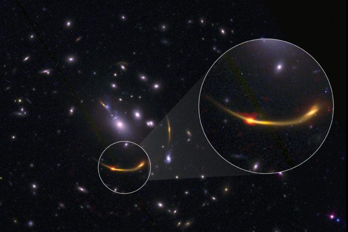 Imagen compuesta del cúmulo de galaxias MACSJ 0138 con datos del Atacama Large Millimeter/submillimeter Array (ALMA) y del telescopio espacial Hubble de la NASA. La sección ampliada muestra un punto rojo anaranjado brillante que representa el polvo frío observado en frecuencias de radio usando ALMA. El polvo frío ayuda a los científicos a calcular indirectamente la cantidad de gas de hidrógeno (necesario par la formación de estrellas) presente en las galaxias del cúmulo. Créditos: ALMA (ESO/NAOJ/NRAO)/S. Dagnello (NRAO), STScI, K. Whitaker et al.