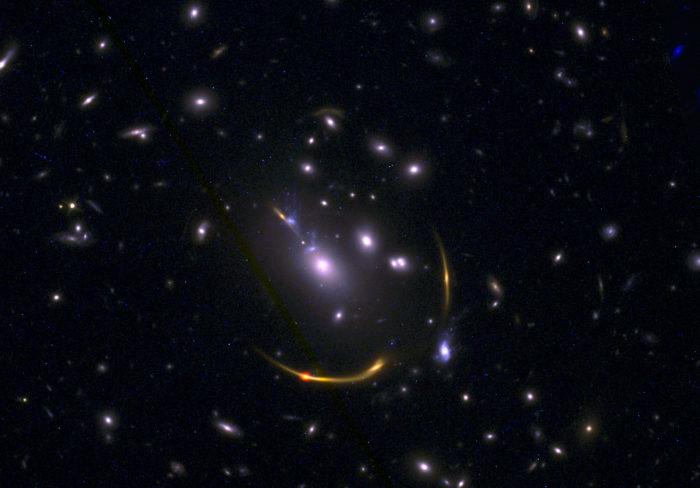 Imagen compuesta del cúmulo de galaxias MACSJ 0138 con datos del Atacama Large Millimeter/submillimeter Array (ALMA) y del telescopio espacial Hubble de la NASA obtenidos en el marco del estudio REQUIEM. Las imágenes de las galaxias masivas del Universo primitivo revelaron que estas carecen del gas de hidrógeno frío necesario para producir estrellas. Créditos: ALMA (ESO/NAOJ/NRAO)/S. Dagnello (NRAO), STScI, K. Whitaker et al.